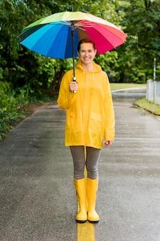 Frau, die einen bunten regenschirm hält