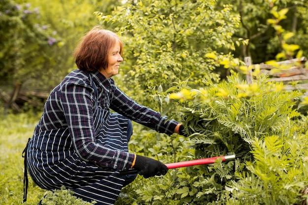 Frau, die einen busch schneidet
