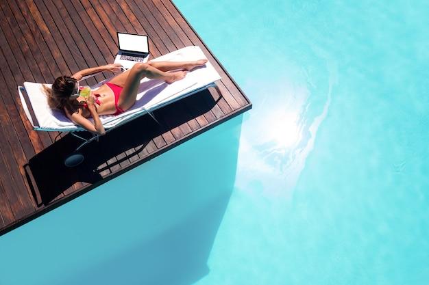 Frau, die einen cocktail trinkt und laptop verwendet