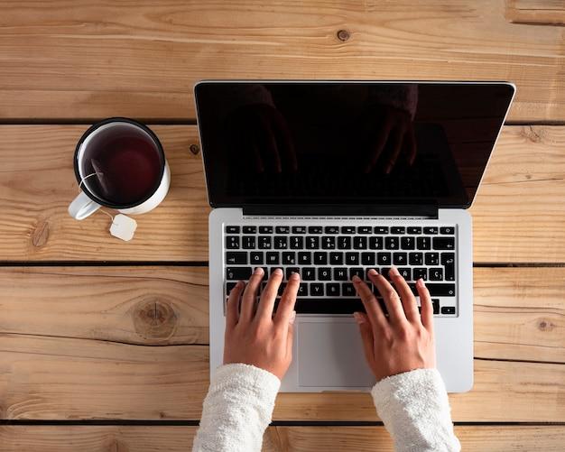 Frau, die einen computer mit tee über einem holztisch benutzt