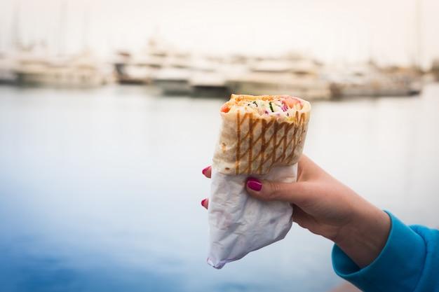Frau, die einen döner kebab in ihrer hand hält