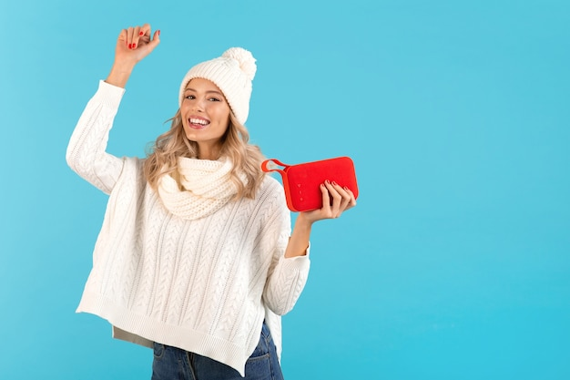 Frau, die einen drahtlosen lautsprecher hält und musik hört, tanzt glücklich mit weißem pullover und strickmütze auf blau