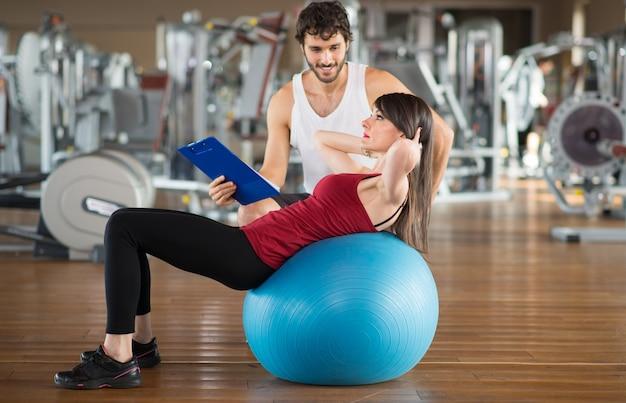 Frau, die einen eignungsball verwendet, um mit einem persönlichen trainer auszuarbeiten