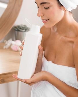 Frau, die einen entspannenden tag hat und eine körperlotion riecht