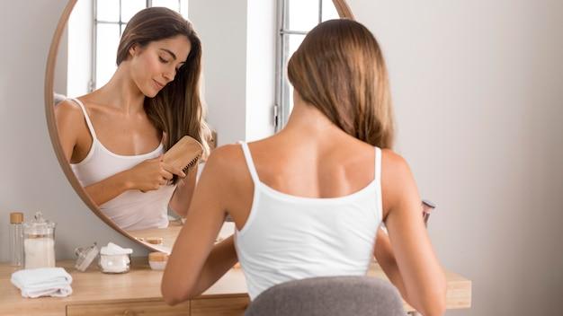 Frau, die einen entspannenden tag hat und ihr haar bürstet