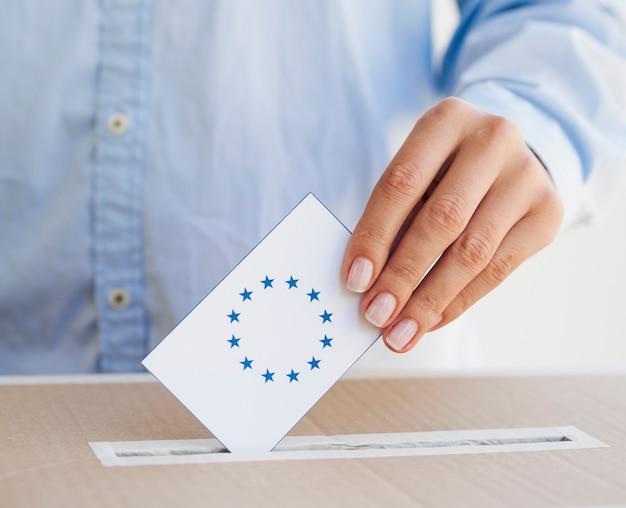 Frau, die einen europäischen stimmzettel in kasten einsetzt