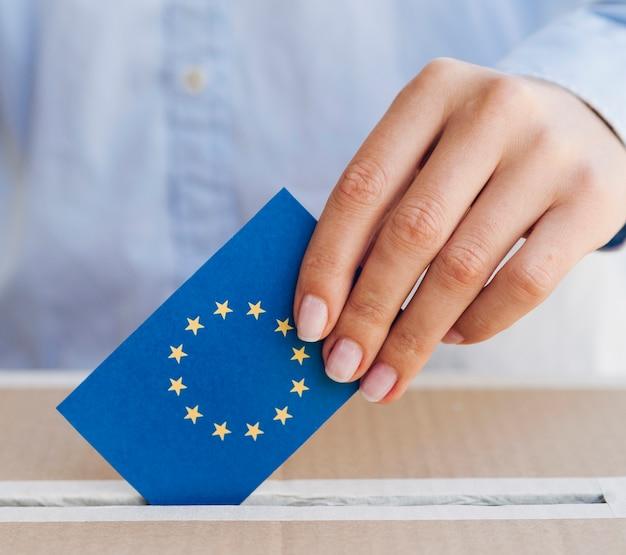 Frau, die einen europäischen stimmzettel in kastennahaufnahme einsetzt
