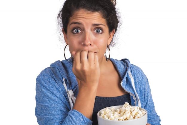 Frau, die einen film beim essen von popcorn sieht.