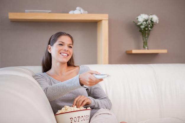 Frau, die einen film mit einer schüssel popcorn aufpasst