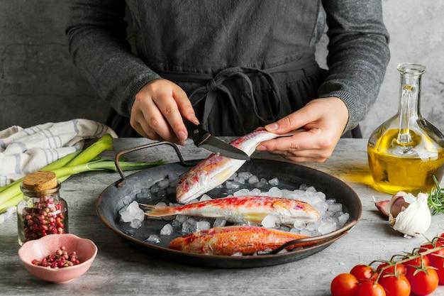 Frau, die einen fisch zum kochen vorbereitet