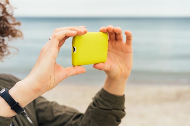 Frau, die einen gelben handy mit zwei händen auf dem strand hält