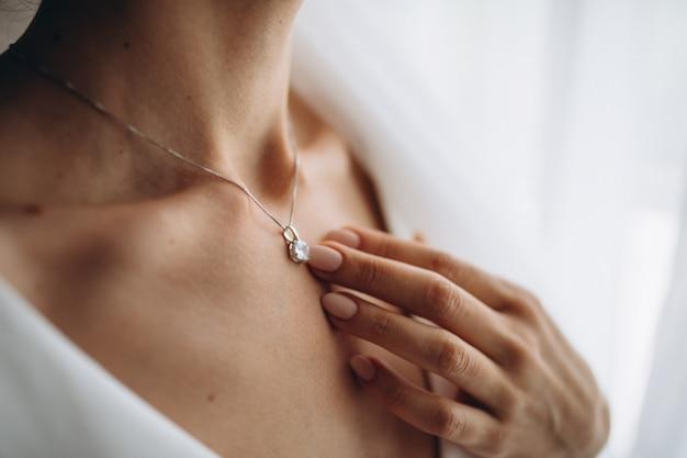 Frau, die einen glänzenden diamantanhänger trägt