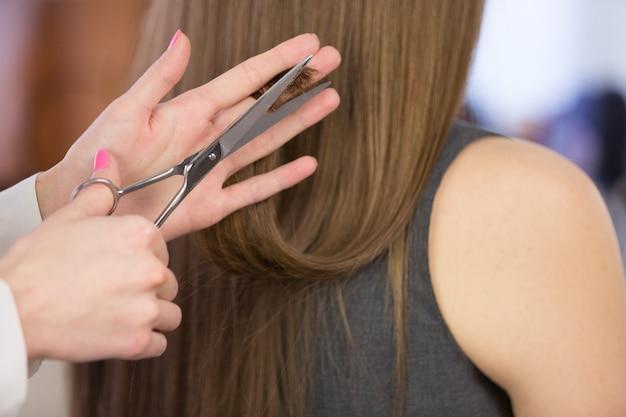 Frau, die einen haarschnitt mit einer schere auf salonhintergrund hat