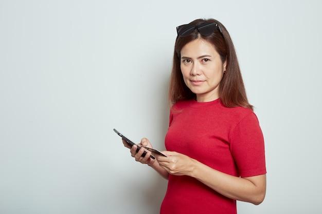 Frau, die einen handy mit kreditkarte verwendet