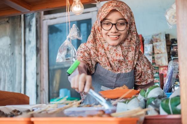 Frau, die einen hijab, einen standverkäufer trägt, lächelt, während sie einen lebensmittelclip hält, um die lebensmittelanzeigen im wagenstand aufzuräumen