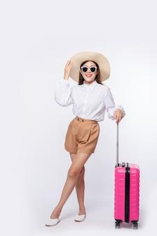Frau, die einen hut, eine brille und die griffe der koffer trägt, um zu reisen
