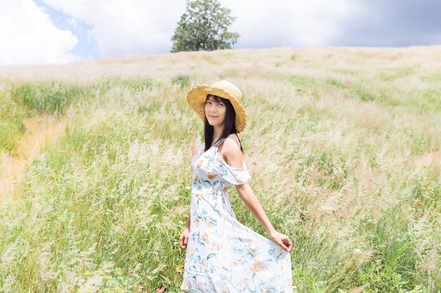 Frau, die einen hut trägt, ein weißes kleid trägt und mitten im gras mit schönen weißen blumen mit einer entspannten und glücklichen stimmung steht.