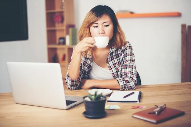 Frau, die einen kaffee bei der arbeit