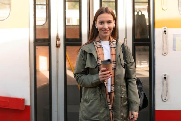 Frau, die einen kaffee im öffentlichen straßenbahnverkehr hält
