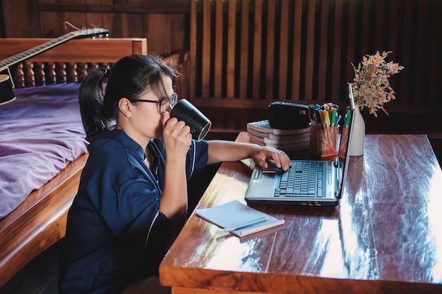 Frau, die einen kaffee trinkt, auf einer etage zu hause sitzt, notizen aufschreibt, öffnete laptop vor ihr.