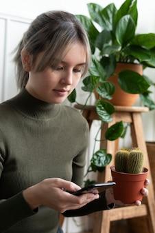 Frau, die einen kaktus trägt, während sie ihr telefon überprüft