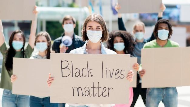 Frau, die einen karton mit schwarzem lebensmateriezitat hält
