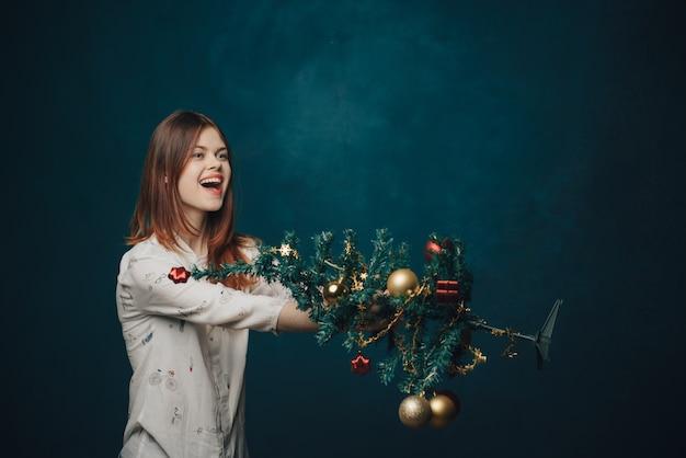 Frau, die einen kleinen weihnachtsbaum hält