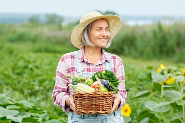 Frau, die einen korb voller ernte-bio-gemüse und wurzel auf bio-bio-farm hält. herbstgemüseernte.