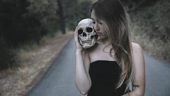 Frau, die einen künstlichen Mannschädel auf der Schulter steht auf Straße hält