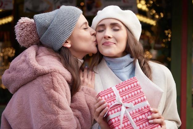Frau, die einen kuss auf weihnachtsmarkt gibt
