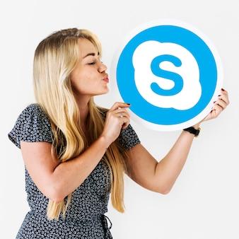 Frau, die einen kuss zu einer skype-ikone durchbrennt