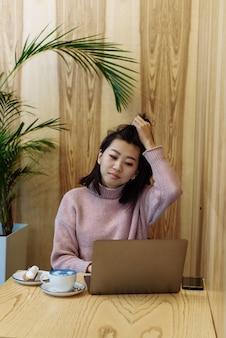 Frau, die einen laptop in einem café benutzt