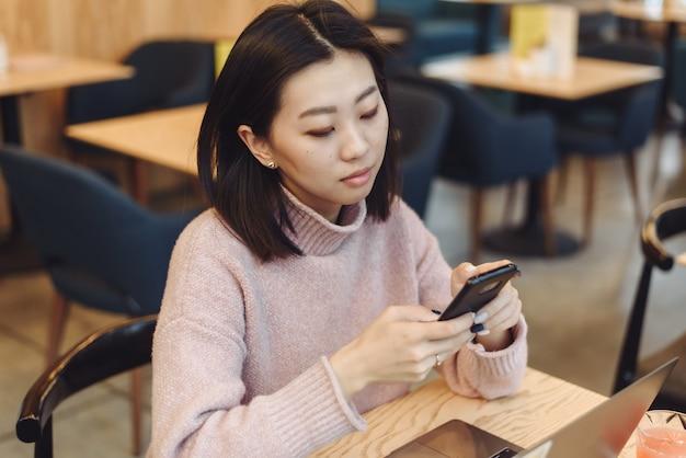 Frau, die einen laptop und ein smartphone in einem café verwendet