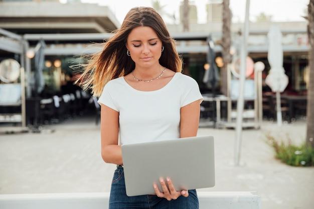 Frau, die einen laptop unten schaut hält