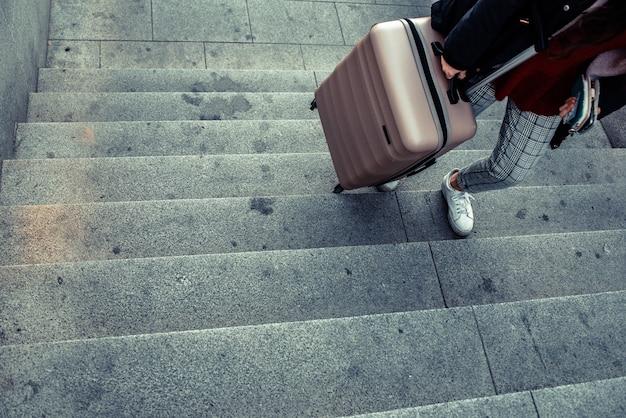 Frau, die einen laufkatzenkoffer schleppt, um die treppe einer u-bahn zu klettern.