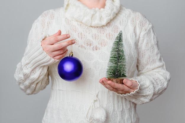 Frau, die einen lila weihnachtsball und dekorativen kleinen baum hält