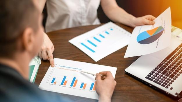 Frau, die einen mann finanzdiagramme auf dem tisch zeigt. laptop, papiere