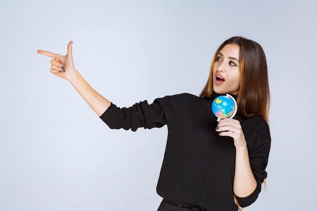 Frau, die einen mini-globus hält und auf irgendwo zeigt.