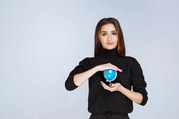 Frau, die einen mini-globus hält und fördert.