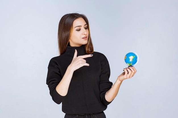 Frau, die einen mini-globus hält und orte darauf findet.