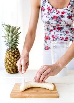 Frau, die einen mittleren bananenschuss schneidet