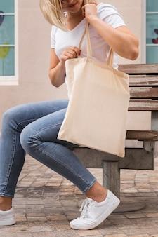 Frau, die einen mittleren schuss der einkaufstasche trägt