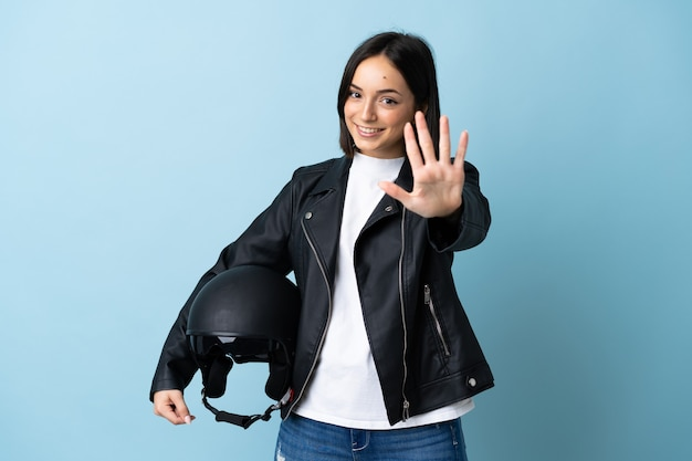 Frau, die einen motorradhelm lokalisiert auf blau hält, der fünf mit den fingern zählt
