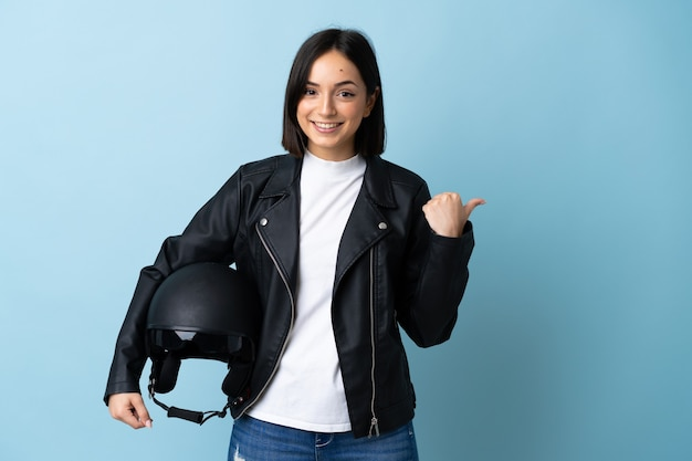 Frau, die einen motorradhelm lokalisiert auf blauem hintergrund hält, der zur seite zeigt, um ein produkt zu präsentieren