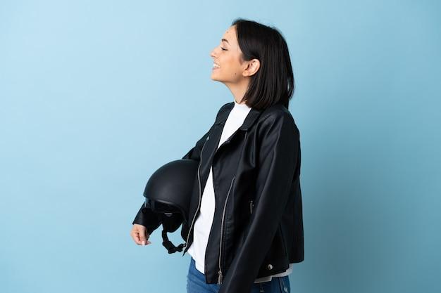 Frau, die einen motorradhelm lokalisiert auf blauem hintergrund lacht in seitlicher position hält
