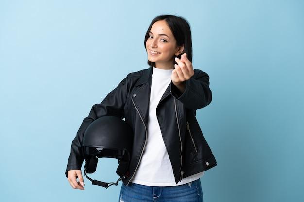 Frau, die einen motorradhelm lokalisiert hält, der geldgeste macht