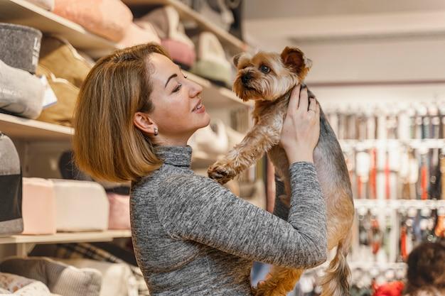 Frau, die einen niedlichen kleinen hund an der tierhandlung hält