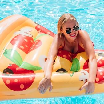 Frau, die einen pizzaschwimmenfloss hält