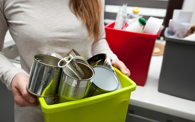 Frau, die einen plastikbehälter mit metallmüll hält