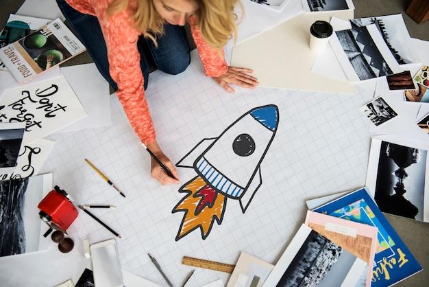 Frau, die einen raketenstart auf einem papier zeichnet